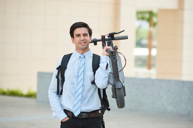 Pracownik biurowy trzymając skuter na zewnątrz