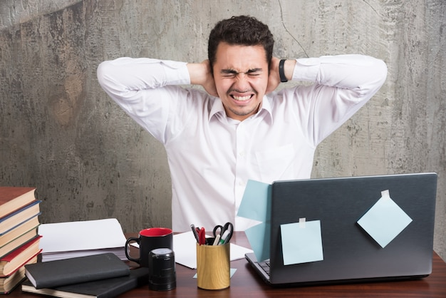 Pracownik biurowy trzymając uszy przy biurku.