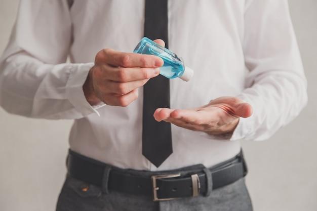 Pracownik biurowy używający tubki dozownika żelu do dezynfekcji rąk, koronawirus covid-19 w miejscach publicznych