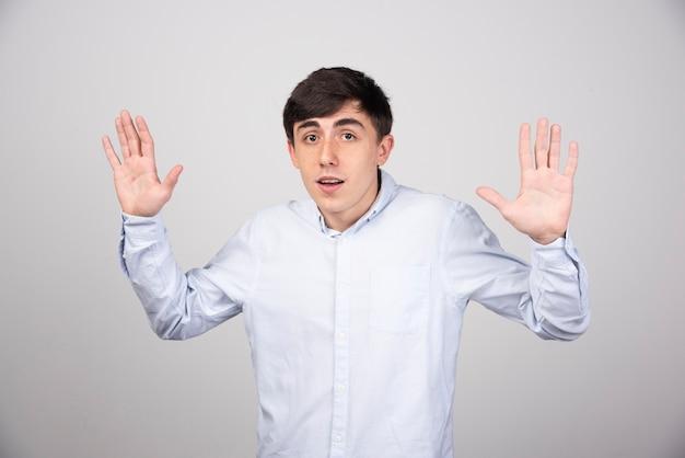 Pracownik biurowy w wizytowym pokazując gest stop na szarej ścianie.
