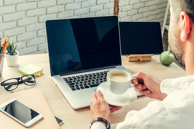 Pracownik biurowy wykonuje swoją pracę siedząc przy stole roboczym z komputerem