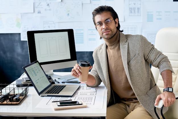 Pracownik biurowy z filiżanką kawy