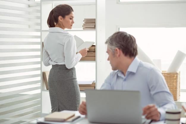 Pracownik biurowy żeński. piękna, przyjemna młoda kobieta stojąca w pobliżu półki i trzymając książkę, patrząc na nią