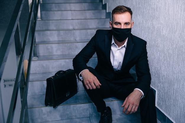Pracownik biznesowy z maską ochronną siedzi na schodach z walizką hist