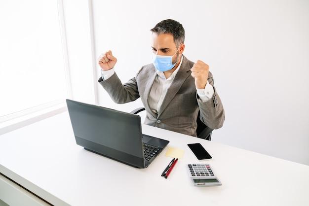 Pracownik biznesu szczęśliwie świętujący osiągnięcie ekonomiczne z maską na twarz z powodu pandemii covid19 z laptopem, kalkulatorem, telefonem komórkowym, karteczką samoprzylepną, długopisami z białym podświetleniem i