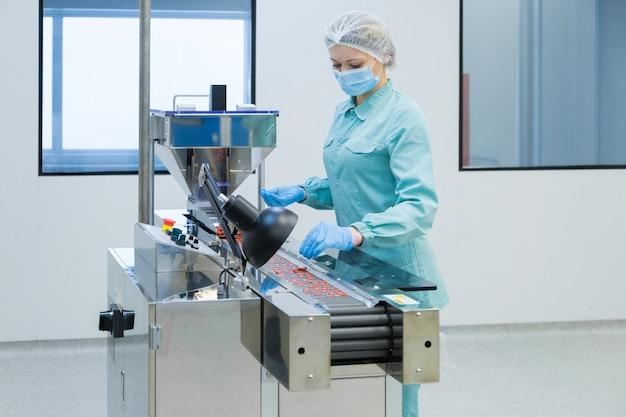 Pracownik branży farmaceutycznej kobieta w odzieży ochronnej obsługującej produkcję tabletek w sterylnych warunkach pracy