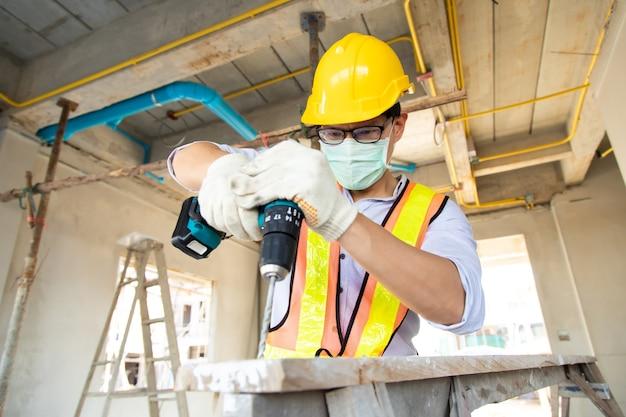 Pracownik brygadzisty budowlanego w kasku ochronnym, wiercenie wiertarką elektryczną na placu budowy. noszenie chirurgicznej maski na twarz podczas epidemii koronawirusa i grypy