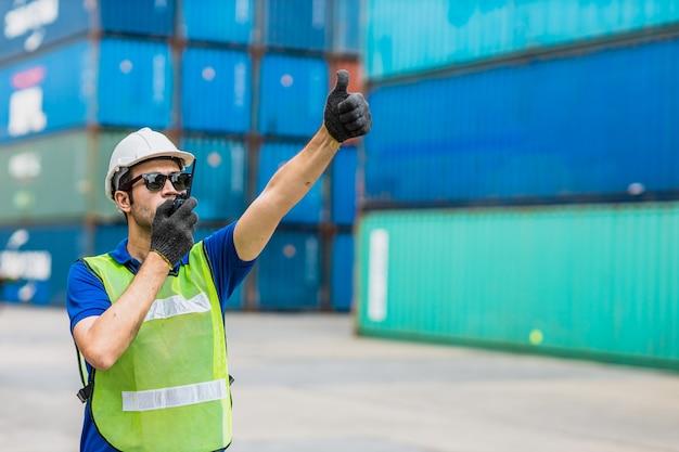Pracownik brygadzisty ds. spedycji pracujący nad kontrolą logistyki załadunku portu towarowego w celu importu towarów eksportowych w magazynie kontenerów.