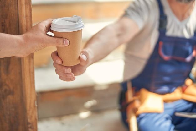Pracownik budowlany daje jednorazowy papierowy kubek swojemu koledze;