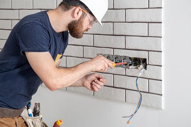 Pracownik budowlany elektryk z brodą w kombinezonie podczas instalacji gniazd. koncepcja renowacji domu.