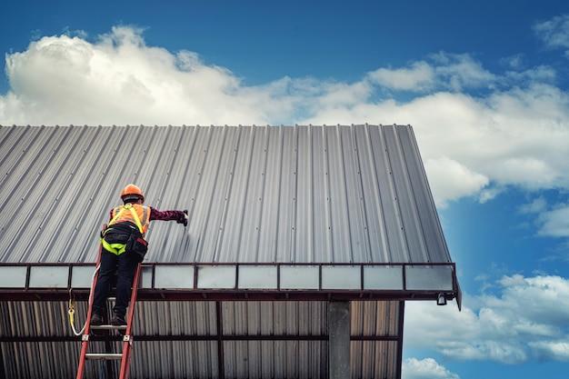 Pracownik budowlany handlowiec na dachu domu z kaskiem ochronnym
