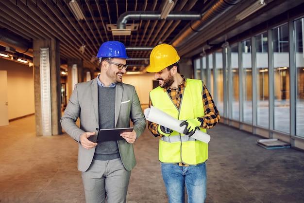 Pracownik budowlany i architekt idą razem po terenie i omawiają projekt, nad którym pracują.