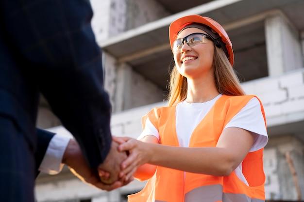 Pracownik budowlany i budowlany na budowie z architektem