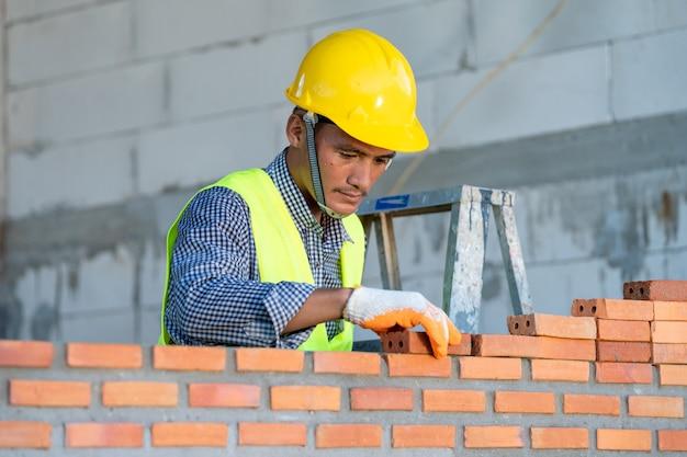 Pracownik budowlany instalacji czerwonej cegły z szpachlą szpachlową do nowego budynku domu na placu budowy