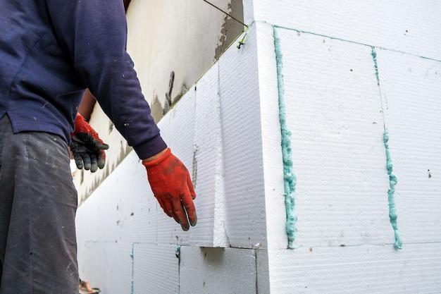 Pracownik budowlany instalujący płyty izolacyjne styropianowe na ścianie elewacji domu w celu ochrony termicznej.