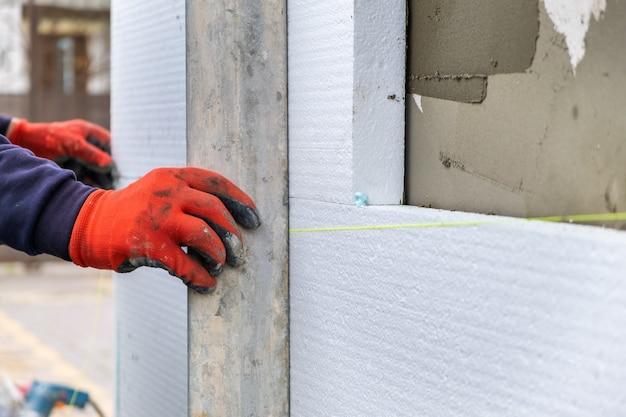 Pracownik budowlany instalujący styropianowe arkusze izolacyjne na ścianie elewacji domu w celu ochrony termicznej.