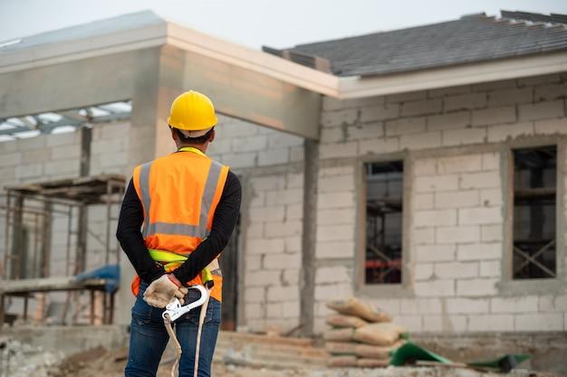 Pracownik budowlany jest ubranym uprząż bezpieczeństwa i zbawczą kreskową pozycję przy budową.