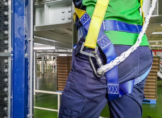 Pracownik budowlany korzysta z uprzęży bezpieczeństwa i liny bezpieczeństwa pracującej na nowym placu budowy