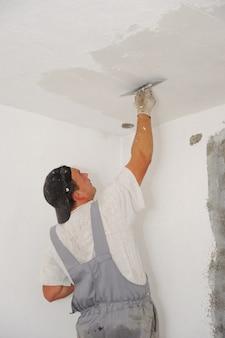Pracownik budowlany maluje ściany