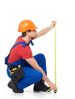 Pracownik budowlany mierzy ścianę na białym tle