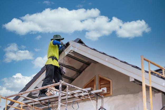 Pracownik budowlany montuje nowy dach z dachówki ceramicznej