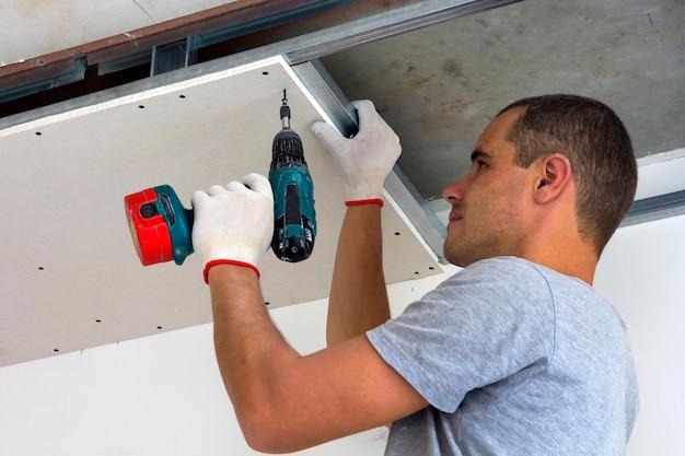 Pracownik budowlany montuje podwieszany sufit z płytą gipsowo-kartonową i mocuje płytę gipsowo-kartonową do metalowej ramy sufitu za pomocą śrubokręta.
