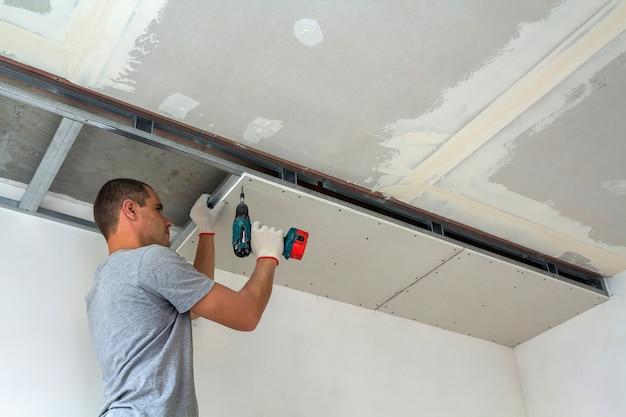 Pracownik budowlany montuje podwieszany sufit z płytami kartonowo-gipsowymi za pomocą śrubokręta.