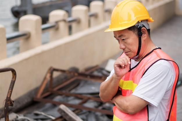 Pracownik budowlany myślenia planowania ze stosu surowca