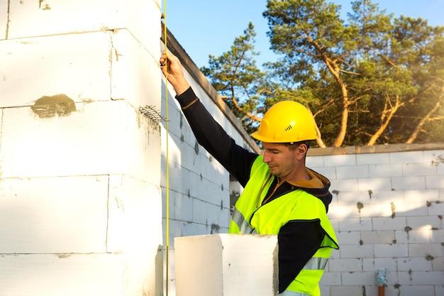 Pracownik budowlany na budowie mierzy długość otworu okiennego i ściany za pomocą taśmy mierniczej. domek wykonany jest z bloczków z betonu porowatego, odzieży ochronnej - kasku i kamizelki