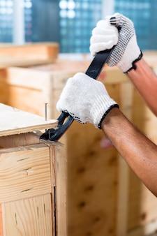 Pracownik budowlany na placu budowy zamyka drewniane pudełko lub pojemnik ładunkowy młotkiem i gwoździem