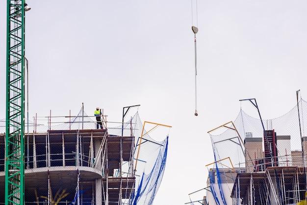 Pracownik budowlany na szczycie budynku w budowie kieruje dźwigiem.