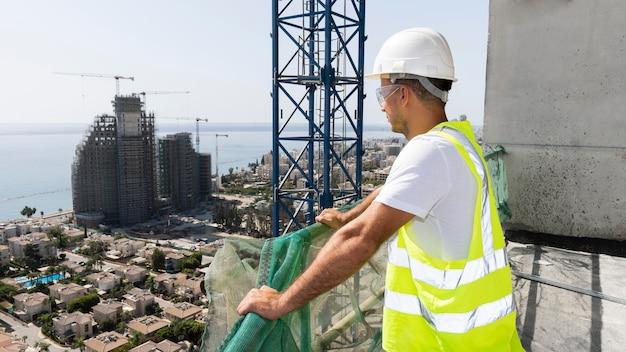 Pracownik budowlany na zewnątrz patrząc daleko
