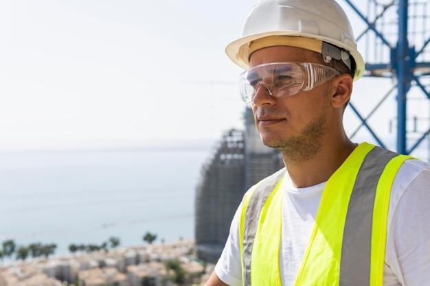 Pracownik budowlany na zewnątrz w okularach ochronnych i kasku