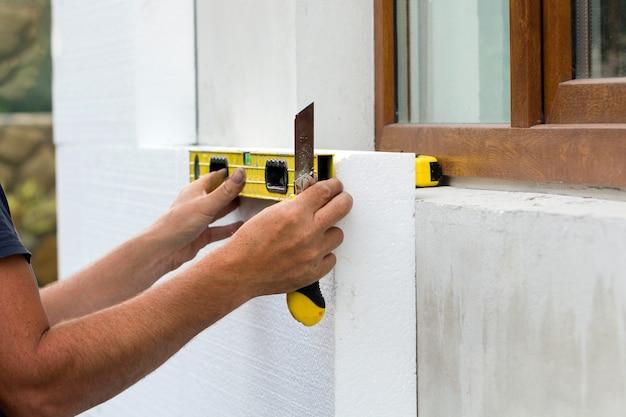Pracownik budowlany ocieplający ścianę domu styropianową płytą izolacyjną.