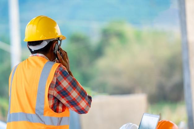 Pracownik budowlany opowiada na telefonie przy budową, inżynier, budowy pojęcie.