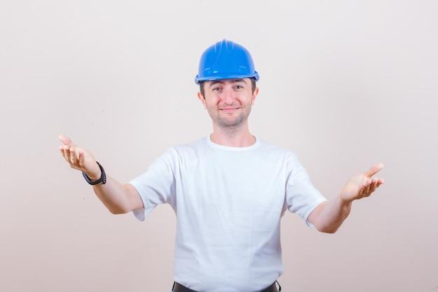 Pracownik budowlany otwiera ramiona, aby przytulić się w koszulce, kasku i wyglądać delikatnie