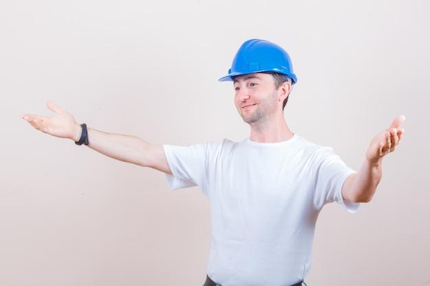 Pracownik budowlany otwiera ramiona, aby przytulić się w koszulce, kasku i wyglądać uprzejmie