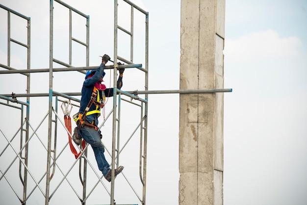 Pracownik budowlany pracuje na rusztowaniu w budowie