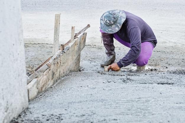 Pracownik budowlany pracuje na tynku cemencie dla ziemi w nowym domu.