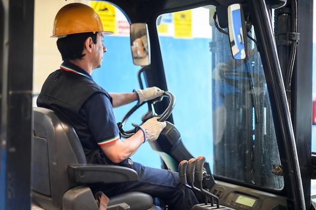 Pracownik budowlany prowadzący wózek widłowy w zakładzie przemysłowym