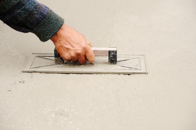 Pracownik budowlany rozprzestrzenia mokry beton
