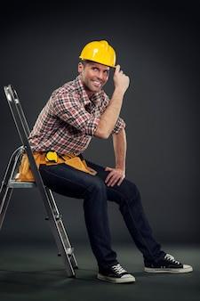 Pracownik budowlany siedzi na drabinie
