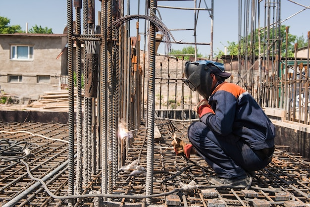 Pracownik budowlany spawanie metalowych prętów zbrojeniowych do wylewania fundamentów. szczerzy, prawdziwi ludzie