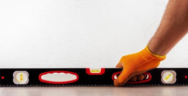 Pracownik budowlany sprawdza poziom konstrukcji podłogi z płytek ceramicznych
