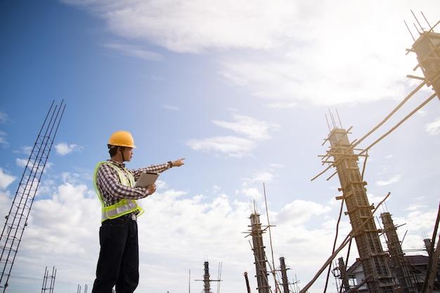 Pracownik budowlany trzyma pastylka komputer i wskazuje lub pokazuje coś