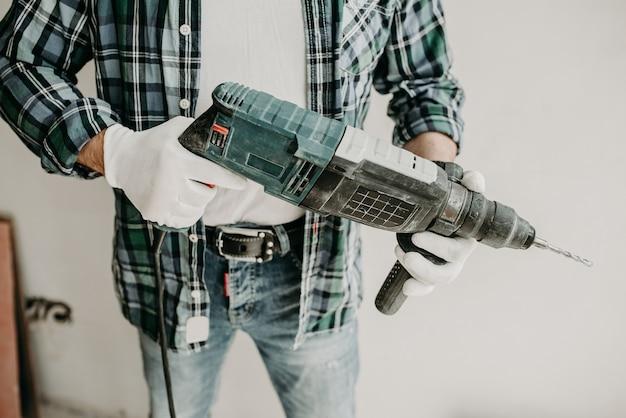 Pracownik budowlany trzyma wiertło w dłoniach