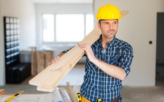 Pracownik budowlany trzymając deski drewniane