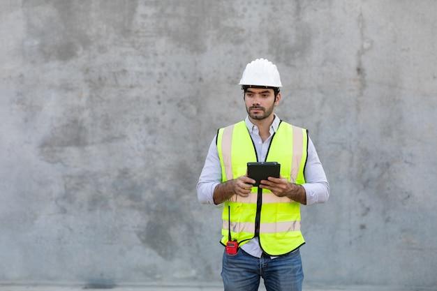 Pracownik budowlany trzymając i patrząc na izolat cyfrowy tablet