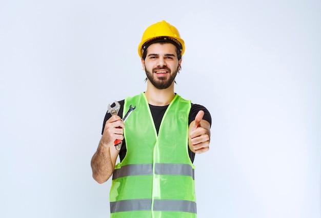 Pracownik budowlany trzymając klucz i klucz i wygląda na zadowolony.