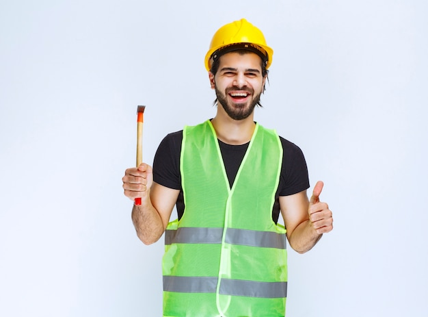 Pracownik Budowlany, Trzymając Młotek Pazur I Pokazując Znak Przyjemności. Darmowe Zdjęcia